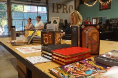 """Mark Russell's books and comics front-and-center while Jenny Forrester plays in the """"creativity corner"""" (all photos by LS)"""
