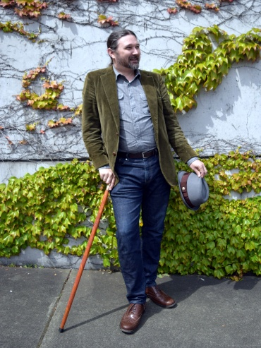"""Author with walking stick, not wearing hat"""