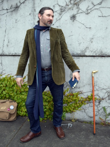 Stupidly long scarf, prop cane and prop satchel, conspicuous writer's notebook.